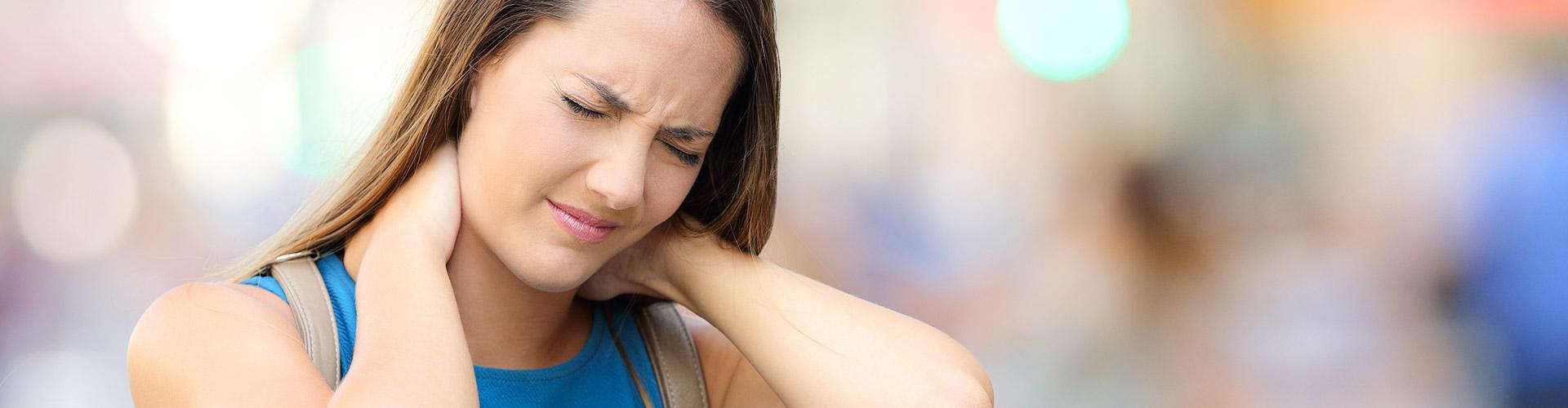 junge frau hält sich nacken vor schmerzen